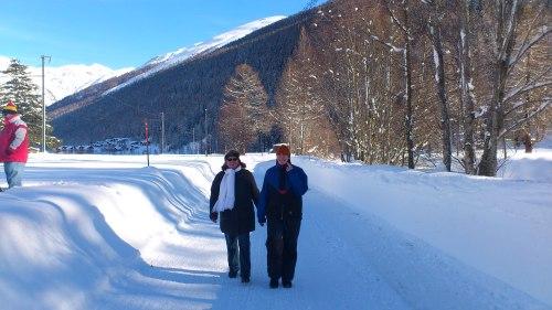 Links een treinspotters, midden in het beeld drie generaties in de sneeuw